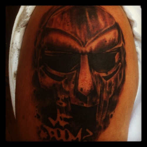 This is my MF DOOM mask tattoo I got done in June By Heath Rave at Speakeasy tattoo.  I got this tatoo because of what the mask represents not necessarily the artists himself(he isnt my favorite artist) the mask represents the dichotomy between what Hip-Hop music is largely about now(how many women you are having sex with,the types of intoxicants you are putting into your body,what brand of clothes you are wearing, etc…. in short everything except the music) and what it was and in my opinion should still be about(the art,the poetry,the music). I chose this version of the mask taken from the cover of the Madvillian album because its such a powerful image.  He wears a mask just to cover the raw flesh a rather ugly brother with flows thats gorgeous~MF DOOM