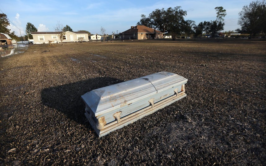 inothernews:  ISAAC'S REMAINS  A coffin that washed up onto a front lawn due to Hurricane Isaac flooding is seen in Plaquemines Parish, Braithwaite, La.  Tens of thousands of residents remain without power nearly a week after the storm struck, according to the Times-Picayune.  (Photo: Mario Tama / Getty Images via The Telegraph)  #HowAboutNo Please, when my time comes, let me be cremated. I think the world can only handle me once. P.S.: send my ashes on a rocket to be spread on Uranus for the lulz. #NotKiddingButItMightBeCheaperJustToSprinkleMeInTheOcean