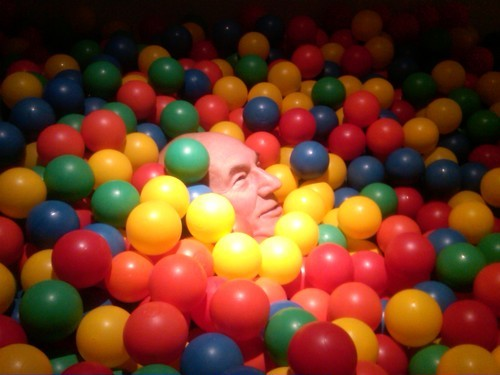 Patrick Stewart's face in a rainbow ball pit.
