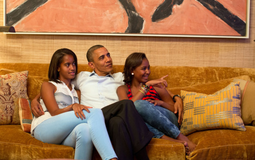President Barack Obama and his daughters, Malia, left, and Sasha, watch on television as First Lady Michelle Obama takes the stage to deliver her speech at the Democratic National Convention (by The White House)