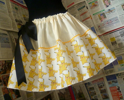 pwnlove:  High Voltage Skirt Wear an electric Pokemon skirt complete with a black satin bow. Extra points if I see a picture of you playing Pokemon while wearing this skirt.  Pikachu Skirt by Rooby