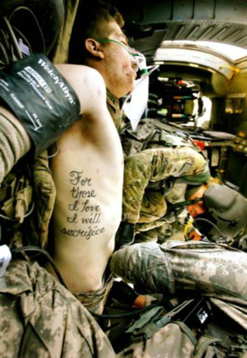 philjayr:  Tattoos are as old as war. Lots of soldiers get them, with military motifs, girlfriend's names, or various guns, skulls or dragons adorning their skin. Some get something less ornate. Private First Class Kyle Hockenberry had For those I love I will sacrifice stitched into his flesh. He had no idea how prescient he was. A member of the 1st Infantry Division, Hockenberry's world changed June 15. He was on a foot patrol just outside Haji Ramuddin, Afghanistan, when an improvised explosive device detonated nearby. In this photograph, by Laura Rauch for the military's Stars and Stripes newspaper, flight medic Corporal Amanda Mosher is tending to Hockenberry's wounds aboard a medevac helicopter minutes after the explosion. Kyle Hockenberry, 19, lost both legs and his left arm in the blast.