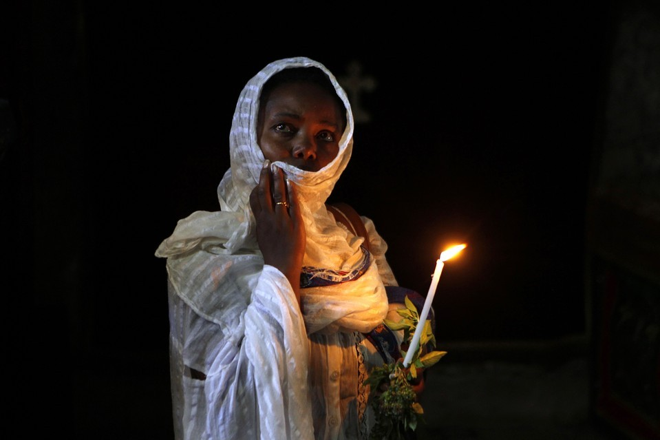 An Ethiopian nun held a candle at the tomb of the Virgin Mary outside Jerusalem's Old City before a procession Wednesday. Orthodox Christians participate in the procession yearly. Baz Ratner/Reuters