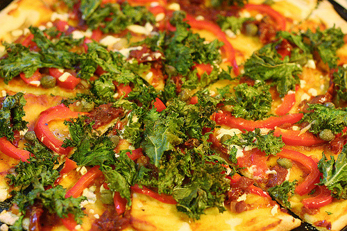 A thin crust pizza with sundried tomato, capers, red pepper, kale, and Daiya cheese! Born & died on Vegan Pizza Day 2012.  CC image via flickr user malloreigh.