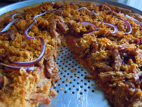 A BBQ Soy Curl pizza with St. Martaen vegan gouda and red onions. CC image via flickr user jaundicedferret.