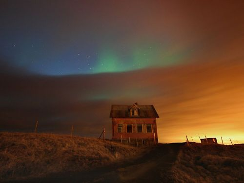 AUGUST 31, 2012 Northern Lights, Iceland Photograph by Fred Schalk, My Shot This Month in Photo of the Day: Your Photos On this night northern lights had been predicted, so I decided to find a nice spot on the Reykjanes peninsula. However, the sky wasn't very cooperative, especially in the far distance, so on my way over I stopped near an abandoned house, where it was less cloudy. In some ways the outcome was really not so bad because the clouds, the blue spots in the sky, the green northern lights, and the orange reflection of the Reykjavik city lights all mixed together in a multicolor light show.