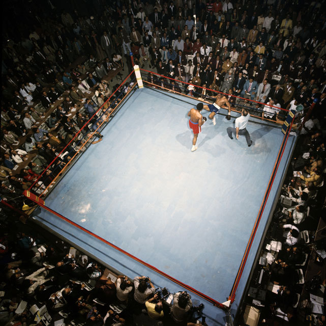 SI photographer Neil Leifer captures the aerial view of Ken Norton on the ropes after being knocked down by George Foreman in the second round of their 1974 fight. Norton was knocked down three times in two rounds, giving a TKO victory to Foreman. (Neil Leifer/SI) SI VAULT: Foreman easily disposes of Norton (4.8.74)