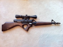 "Calico M-100 The carbine version of the M-110, it still has the .22 LR caliber. Calico's fell victim to the Assault Weapons Ban and had to conform to the new laws. This one sports the wood furniture in a less aggressive look. Note the rather rare factory scope mount. Unlike the 9mm versions which eject spent cases downward, the .22 LR models eject from the side like regular rifles and handguns.  So its the same gun with the same capability's as the other one but now they have slapped a few curves and some wooden furniture and now its just fine. Honestly I don't know why Governments are so retarded. ""Oh no it looks scary so lets ban the shit out of it"" I mean come on thats just stupid."