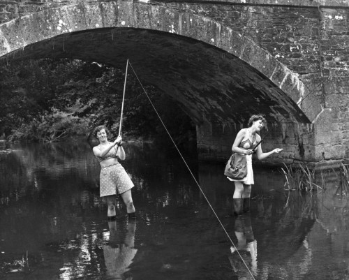 Two women on holiday from London try their hand at trout fishing in the River Tamar in Cornwall, near North Tamerton, where it joins the River Deer. 18th August 1951.