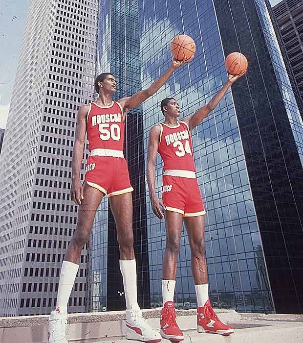 Here's an old photo of the Houston Rockets Twin Towers tandem of Ralph Sampson and (H)akeeem Olajuwon standing in front of the Twin Towers.  Today is the day Don Nelson, Reggie Miller and also Ralph Sampson will be inducted into the Naismith Memorial Basketball Hall of Fame in Springfield, Massachusetts.  History hasn't been that kind to the 7-4 Sampson from the University of Virginia. Coming out of college in 1983, he had already graced Sports Illustrated 6 times in just 4 years (here's his first cover as a pro) and was easily the most anticipated professional big man of his generation. Expected to be equal parts Russell and Chamberlain, the lithe Sampson was an agile big man that could play from the perimeter before it was cool to do so.  In his first two seasons in the NBA, he averaged over 21 p.p.g. and 10 r.p.g while shooting over 50% from the field. He also played every one of the Rockets regular season games. They would be the only seasons he did so over the course of a 9-year, largely disappointing career where he and (H)akeem never won a title—getting closest in 1986 when they reached the Finals after Ralph's incredible buzzer-beater against the favored Lakers in the Western Conference Finals, but ultimately falling to Bird, Walton and that dominant '86 Celtics team in the Finals.  Since it's Hall of Fame week in a largely boring September for NBA fans, there have been a few posts about Mr. Sampson, largely debating whether he deserves inclusion in the Hall after such a lackluster pro career that didn't even span a decade. The best is probably Kelly Dwyer over at BDL, but Kurt Helin has some video highlights of Ralph at PBT, Slam republished their Q & A with Sampson(sonite) from Slam 41 and Scott Howard-Cooper talks about Sampson's attempt to become a coach.