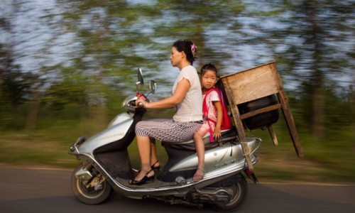theweekmagazine:  A mother, daughter, and table ride a motor scooter to Nangang Primary School in rural China. Out of the 5,000 students who live in this rural township, about 3,000 had to bring their own desks and chairs to school.  PHOTO: Imaginechina/Corbis 12 of this week's best photos