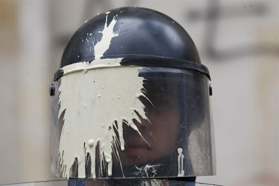 politics-war:  A riot police officer, with a helmet stained by thrown paint, watches a march of teachers and students protesting a wide range of issues regarding the government's educational policies in Bogota, Colombia, Sept. 5.