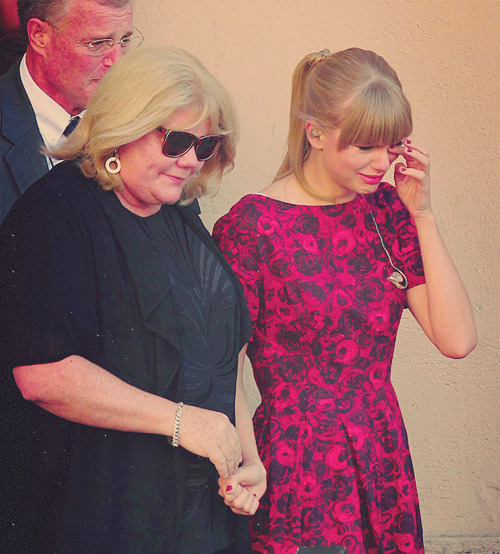Taylor outside the 'Standing Up To Cancer' event, supported by her parents.
