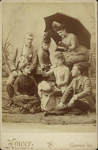 ca. 1885, [cabinet card, portrait of six well-dressed young people, all gazing at a small object, possibly a small coin or gold piece, held up by the woman at center], Hower via Christopher Wahren Fine Photographs, Skylight Gallery #34