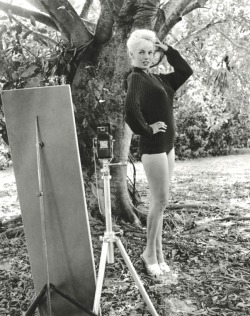 "Bunny Yeager was Florida's most stunning and sought after model. ""I was never a pinup model,""she was quick to point out. ""I did not pose for men individually like Bettie Page did."" Bunny made a name for herself as a fashion influencer as well– designing and donning her own two-piece bathing suits.  ""All the other models were wearing one-piece Jantzen and Catalina suits. I made my own and am beginning to think I invented the bikini, after the French did it."""