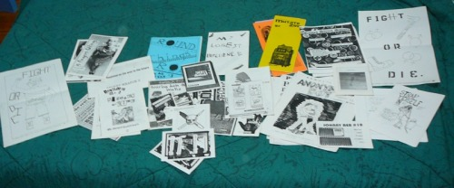 "[image: various queer & trans* punk, feminist, skinhead, etc zines in black and white or color, and hand-drawn posters and Xerox Revolutionaries Distro promotional materials, spread out over a dark green and black comforter.] So, I have a whole mess of various queer, trans*, feminist, punk, skinhead, etc. zines from Xerox Revolutionaries Distro that Hank sent me years ago after he stopped running that distro. Figured I'd see if anyone wants any of them. I can do little ""grab bags"" or send them out individually, whatever folks wanna do. None of these zines are on my distro, they were all on Xerox Revolutionaries, and I only have single copies of each issue of the zines. Whichever ones are leftover that I don't donate to Sherwood Forest Zine Library & Bookshare (a new zine library & bookshare starting up in Austin, TX) or keep for myself, and that are not claimed by someone else, I will send to QZAP if they want them. (Support QZAP! They're an awesome zine archive project with LOADS of queer/trans*/bi/pans/les/gay/etc zines available to download for free, read online, etc. Wonderful, wonderful resource.) If folks who want zines can send me a little money for the shipping, that'd be great cuz I'm broke as shit, but if not that's okay. The zines are totally free (or if you wanna do a trade, that's fine, too. either way). I don't have all the zine titles written down yet, but when I do, I'll post here again and people can pick which ones they want. Also, please know I am not endorsing any of the zines, not saying I agree with their content, or anything like that, and I haven't read them all in a while so I don't remember if they're triggering so read with caution or whatever. Oh, the posters and stickers (not pictured) are up for grabs as well. P.S. In order to get all the zines in the picture (above), I piled zines on top of each other, so you can't tell that I have several issues of some of the zines."