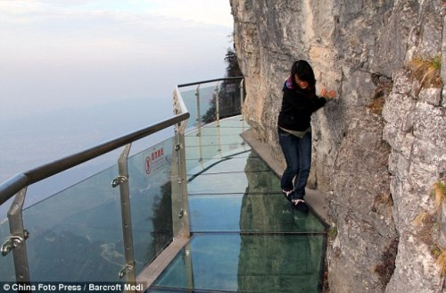 China's newest tourist attraction… a glass-bottomed walkway around a cliff face   On one side a sheer rock face, on the other a 4,000ft drop - and all to separate the brave traveller from a deadly plunge is a 3ft-wide, 2.5in thick walkway.  Tianmen Mountain in Zhangjiajie, China.