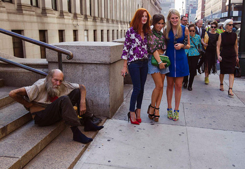 politics-war:  Fashionistas pose for photographs in front of a homeless man outside Moynihan station following a showing of the Rag & Bone spring/summer 2013 collection during New York fashion week. Photograph: Lucas Jackson