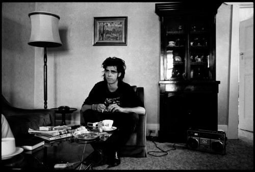 [B/w photo of Nick Cave, apparently in a living room]  The boom-box is fine, it gives him something to do, but how the hell he got a china cabinet into the enclosure is beyond me.
