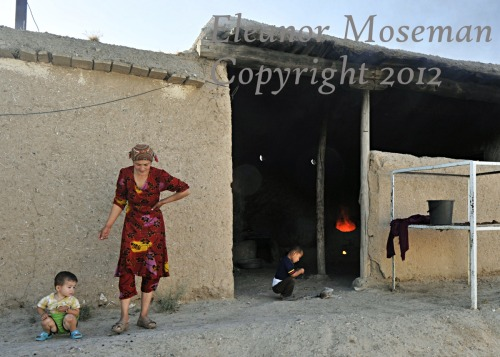emoseman:  Uzbek mother takes care of her child and another during the morning's preparation of naan. Uzbekistan, 2012