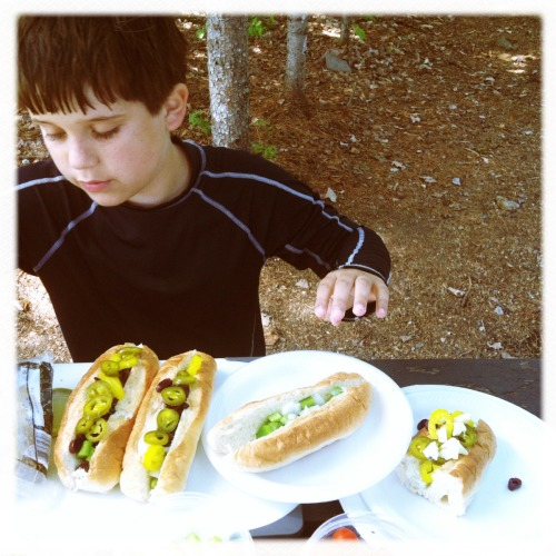 Maine Meal Redux As a child, I enjoyed a plethora of submarine sandwiches, which are called Italian sandwiches in Maine. There was little more exciting than picking up one of these 'fancy' (i.e. store bought) sandwiches, a soda, and a bag of salt and vinegar chips before heading off to the lake. This summer my older son fell in love with these sandwiches too, and as he is on a DIY kick, insisted on making them himself for various family members on multiple excursions. He became quite skilled at it, settling on a combination of extra sharp cheddar, ham, olives, pepper, onion and tomato, and dressing them with the traditional oil and vinegar. It is helpful to have a picnic table available during assembly, but not absolutely necessary.