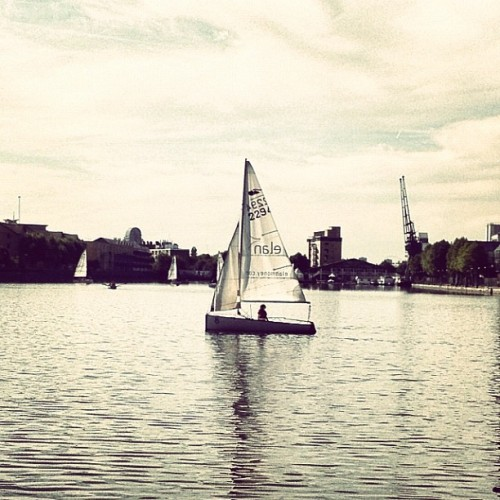 Sailboat • #docklandssailingcentre #millwallouterdock #londondocklands #isleofdogs #eastlondon #london #england #greatbritain #unitedkingdom #dockside #waterside #whitecloud #reflection #sailboat #cranes #eastend #afternoon #september #2012 #brannan #lux  (Taken with Instagram at Millwall Outer Dock)
