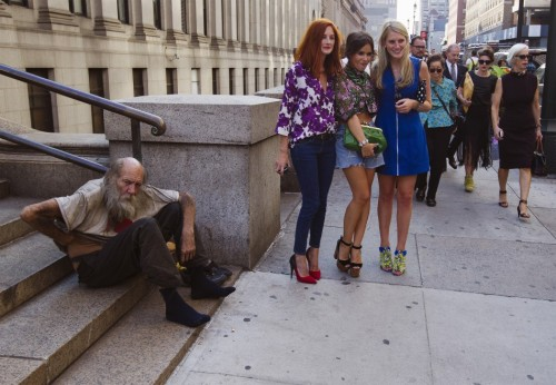 fotojournalismus:  Fashionistas pose for photographs in front of a homeless man outside Moynihan Station following a showing of the Rag & Bone Spring/Summer 2013 collection during New York Fashion Week September 7, 2012. [Credit : Lucas Jackson/Reuters]