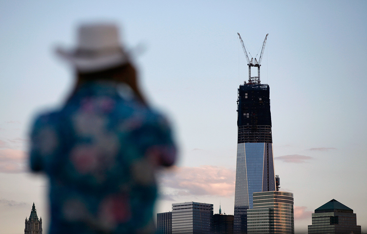 From One World Trade Center: Construction Progress, one of 33 photos.  One World Trade Center stands tall on the skyline of New York's Lower Manhattan as a man takes a picture from a pier in Hoboken, New Jersey, on September 9, 2012. The price tag for the skyscraper was valued at $3.8 billion earlier this year, making it the world's most expensive new office tower. Most of the cost overruns are due to the security measures being taken in the design of the building which sits on a site that has been bombed twice by terrorists. To offset the costs of One World Trade Center, which is being built by the Port Authority of New York and New Jersey, higher bridge and tunnel tolls have been instated and there has been a reduction in spending on transportation infrastructure. The 1,776-foot skyscraper is expected to be completed by late 2013 or early 2014.(Reuters/Gary Hershorn)