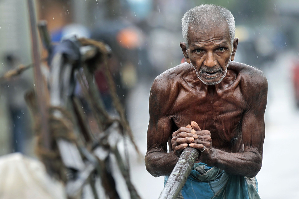 qmannola:  A laborer pushed a cart in the rain in Colombo, Sri Lanka