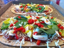 The homemade veggie pizza I made for G and I for lunch over the weekend, ready for some oven lovin' and loaded up on goodness: roasted red peppers, pepperoncini, spinach, mushrooms, fresh garlic, artichokes, and mozzarella cheese.  I think yes!