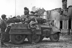 demons:  An M8 scout car of the 3rd Armored Division observing enemy positions somewhere in northern France.