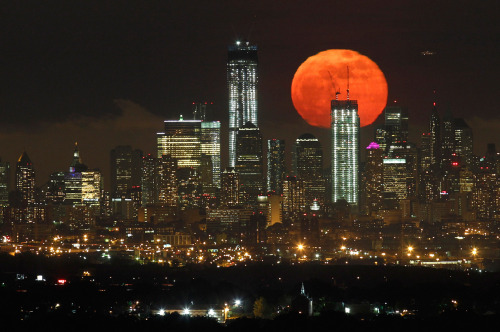 A full moon, as seen from West Orange, New Jersey, rises over the skyline of Lower Manhattan and One World Trade Center in New York, on May 6, 2012.