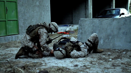 Scene: Battle of Fallujah  Michael Joseph/'Gunny' the U.S. Marine Sniper, sadly looking down upon Rico Reid/ Eric, his Spotter, his best friend, his brother in ways that transcend the bonds of family, now bleeding to death along with him.