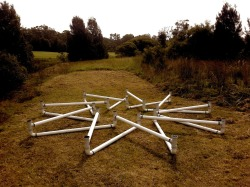 Xpandourossa_systemica_#1. (2012) Finalist in Sculpture on the Greens (Wyong) -  Xpandourossa_systemica #1 portrays a graphic tag as a conundrum of growth within a closed (natural) system. Conceived to rest quietly and red-bellied in the sun on cropped grass the work is a reference to the Ouroboros mythological circled-snake symbol of natural cycles, unity and eternity. As a timeless rosette pattern this continuous 'closed-loop' appears to be able to expand and contract, with a scissor-like motion. Potentially flexible to change shape whilst rigid in form the device is a universal mathematical microcosm. Acknowledging interlocking geometry of Islamic taprats this expresses lessons from 'nature' on growth being within renewing cycles rather than from our anthropocentric constructs. Our desire for control of nature is suspended during the installation as the embracing lawn grows through the structure, tantalizing viewers to question the installation, possibly to wish to modify, snip and clip (scissor cut) the grassy context. The work is analogous to pre-conceived urges to manipulate our natural support systems, and habitats of other species. The figurative snake in the grass, which is a favorite criticism of the artist. To be exhibited from 12 Oct at Heritage Rose Festival - Ruminations Rumsey Art Walk https://www.facebook.com/events/469303429771265/