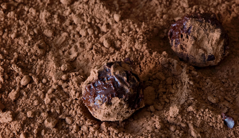 Chai Tea TrufflesMakes about 15 truffles  Ingredients 4 oz (113 g) dark chocolate bar 1 tbsp nonsalted butter 1/4 cup (2 oz) heavy whipping cream 3 tsp Chai Spice black tea Coating (nuts, shaved chocolate, cocoa powder, sprinkles)  Directions 1. Chop up the chocolate and set aside in a heat-proof bowl. Combine the butter, cream and tea (loose or in a cheesecloth sack) in a small saucepan over medium heat. After bringing the mixture to just boiling, take the saucepan off the heat and let it sit for a couple of minutes.  2. Strain out the tea leaves, then pour the cream over the chopped chocolate and stir. The chocolate should be completely smooth; if not, heat it up in a microwave for 20 seconds. Cover the bowl and leave in the refrigerator for several hours, until the chocolate is firm.   3. Once firm, use a spoon, melon baller or your hands to form the chocolate into small balls. The chocolate will begin to melt upon contact, so make sure you have your coating ready. You can use anything as coating; just roll the truffles in it.  4. Keep the truffles in the refrigerator on parchment paper or a plate until they're firm, then serve.
