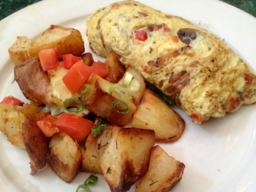Omelette with mushrooms, tomatoes, fresh herbs, sautéed onions, and goat cheese, with roasted potatoes @ Tartine, NYC