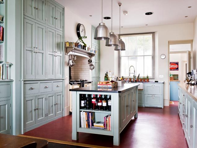 Floor-to-ceiling cabinetry might seem a little inconvenient (especially if you're short like me!), but it looks so majestic! This kitchen has an old vibe to it with the wooden cabinets in that icy blue color and the exposed brick near the stove tops. I love the metal accents to give that little punch of modernity and, of course, I love that easy-to-access storage shelf for all that wine!