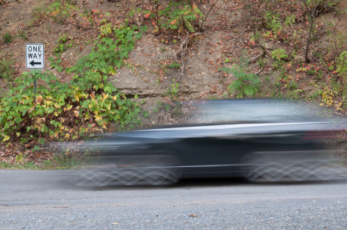 Car travelling down a rural road in WV.  Slow shutter speed to blur car.