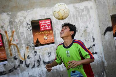 "unicefuk:  A boy heads a football, in the Bhawani Chali neighbourhood of Karachi, Pakistan. The poster behind him is about polio preventio, and the boy is preparing to compete in the first-ever ""United Against Polio"" football tournament to promote immunisation. Find out more about UNICEF's work on immunisation"