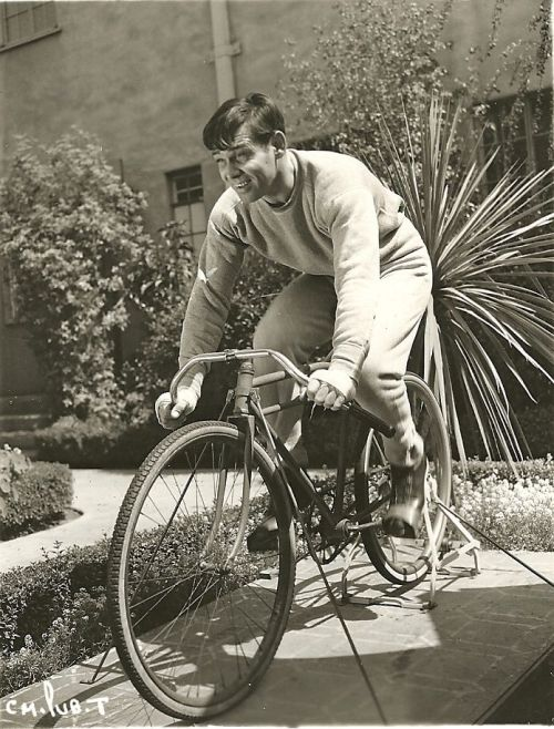 Clark Gable rides a bike. Stationarily.