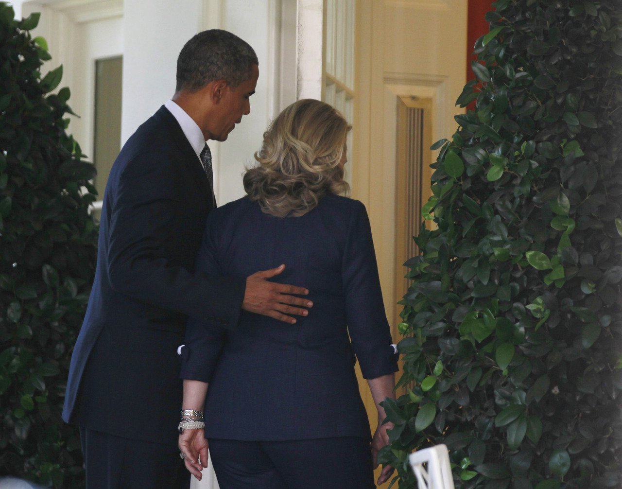 U.S. President Barack Obama and Secretary of State Hillary Clinton walk back into the Oval Office after Obama delivered remarks following the death of the U.S. Ambassador to Libya, Chris Stevens, and others, in the Rose Garden of the White House in Washington, September 12, 2012. [REUTERS/Jason Reed]