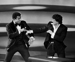 "theacademy:  ""You stole my script!""  Muhammad Ali takes playful jabs at Sylvester Stallone during the 1976 Oscar Ceremony.  That year Stallone was nominated for an Academy Award for Best Actor in a Leading Role AND Best Screenplay for the first installment of the ""Rocky"" franchise. Photo Credit: The Academy"