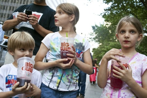 "New York City bans sales of large sugary drinks  JUST IN: New York City's Board of Health has approved a ban on sales of sugary drinks in containers larger than 16 ounces. This is the first restriction of its kind in the U.S., The New York Times reports.Photo: From left, Benjamin, 8, Alana, 10, and Sara Lesczynski, 8, of New York hold ""Big Gulp"" drinks while protesting the proposed ""soda-ban"" that New York City Mayor Michael R. Bloomberg has suggested in New York on July 9, 2012. (Andrew Burton / Reuters)"