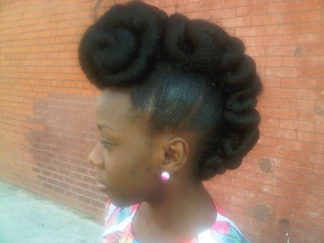 Natural Hair on The Corner- Intricate Updo I walked pass this girl yesterday and had to stop and ask her to take a picture. She was just a pint sized lil thing but her hair made her look 6ft tall. I mean the hair had a life of its own. Imagine someone walking around with this hair in jeans and a tee. I loved it. I think its very creative and would make for great photo shoot hair. Upon getting closer I realized the top twisted part was created with synthetic braiding hair.  Would you try this ladies?