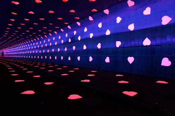 mydarkenedeyes:  Studio Vollaerszwart. For the Glow Festival in Eindhoven, Studio Vollaerszwart transform a bicycle tunnel into a tunnel of love. Thousands of heart-shaped stickers on the ceiling, walls and pavement form a dazzling visual spectacle. The existing lights are replaced by blacklights. This lightens up the fluorescent stickers in the dark tunnel and the hearts seem to seperate from the substrate.