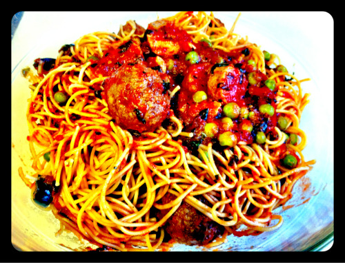 "Vegan spaghetti and meatballs! Well, I was going to make a pasta puttanesca, but went with a hybrid standard spaghetti and meatballs instead.  I like to load up pastas so they're not so boring and there are some added nutritional benefits.  Thinks like faux meatballs and veg sausage add some extra protein.  The peas and spinach add some extra greens into the mix.  Here's what I made tonight… What you need… 1 box spaghetti(I use multigrain) 2 cans crushed tomatoes 3/4 cup kalamata olives 1/4 cup green olives 2-4 cloves garlic(depending on taste) 2 tbsp olive oil 2 Italian veg sausage links(I prefer Tofurkey brand) 1 package of vegan meatballs(frozen or I made my own using ground ""meat"" by Gimme Lean, rolling them up into little balls and baking at 400 for 10 minutes) 1 cup frozen peas 1 cup chopped spinach How to make it… Boil the pasta, I take it off when it's considered ""al dente"" or somewhat still firm. While that's happening, chop and sautee the garlic in the olive oil.  When the smell gets strong and the garlic starts to turn gold, add in crushed tomatoes. Add the meatballs and sausage and simmer sauce on medium for 10 minutes. Add peas, olives, spinach and simmer another 10 minutes or so.   Add sauce to pasta as desired and devour."