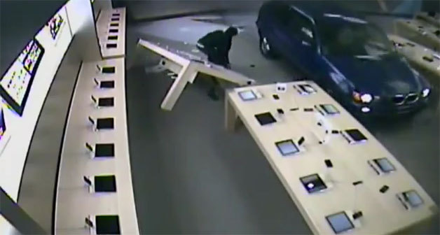 """Apple Store fights back against BMW X5-driving burglars"" A Los Angeles man is being accused of using his 2003 BMW X5 as a battering ram to break into an Apple Store in Temecula, CA last week. The morning robbery on September 6 was caught by surveillance cameras, which show the BMW barreling through the store's glass front and a number of masked men hopping out to snatch iPhone and iPad display models.What the LA driver didn't anticipate was the Apple Store not giving up its goods without a fight. After the BMW went grille-first through the glass, a security gate dropped down, trapping the criminals and their getaway car inside. The video below shows the driver repeatedly ramming the gate with his BMW, pulling forward and knocking over displays covered in iPhones, iPads and computers each time to do it.The driver eventually extricates his X5 from the Apple Store, but the CUV was in such bad shape that police report it didn't make it far from the scene. Having to deal quickly with two flat tires, the driver and his crew reportedly swapped out one for the spare and visited a nearby 7-11 to steal some Fix-A-Flat. The accused driver, Equonne R. Howard, was detained near the scene of the crime a few hours later. Police think he returned looking for his license plate that fell off in the kerfuffle with the security gate.Howard is being held on $600,000 bail, which is what reports say the damage to the Apple Store is estimated at. He's been charged with enough counts to fill two pages of complaints, which include vandalism, burglary and theft of electronics. Apple Store burglaries have become increasingly common as the popularity of the company's products has gone meteoric, but we've never seen one botched so thoroughly, nor one that clumsily uses a BMW to pick the lock. ____________________ #NoEsc"