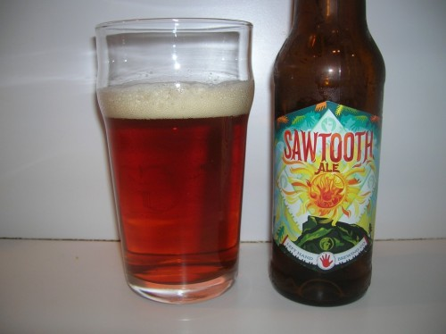 #408: Sawtooth – Left Hand Brewing Company, Longmont, Colorado The first time I ever had this beer, it was nitrogenated. True story. I was at Barcade in Jersey City, and I arrived just in time to sip the leftovers of Left Hand's tap takeover there. One such leftover was Nitro Sawtooth. I enjoyed it quite a bit. Let's see how it is in the bottle. It's brewed with Pale 2-row, Crystal, Munich, Wheat and Black Malt, and hopped with Magnum, Willamette, US-Goldings and Cascade. Checks in at 5.3%. I think I'm finally starting to master this slow pour down the middle thing. I mean, check that beer out. Would you assume I'd poured it down the middle? I think not. Moving on, we've got a rich, coppery-looking, amberish beer here, well-filtered, while maintaining a great deal of that lovely deep color, and all capped off by a sturdy off-white head. Aroma suggests a balanced beer. Green, grassy, herbal hops lay above the rim in somewhat muted fashion. Adore it. Balance, balance, balance. That's the ticket, dear boy. There's a malty wave of flavor up front, folding itself over the palate and bringing rich, sweet flavors of biscuit and a touch of toffee, and perhaps a little buttery caramel as well. In between the malty wave are notes of hoppy brightness, adding much-needed bitterness to smooth things out as well as bringing earthy, almost minty flavors to the party. Malt and hops. Working together. There's a bit of a marmalade thing going on as well, as it smooths out brilliantly towards the finish, capping it all off with a pleasant, slightly crisp dryness. The Verdict: Fruity, caramelly, with enough of a hop bite to level it all out. Easy, enjoyable drinking.