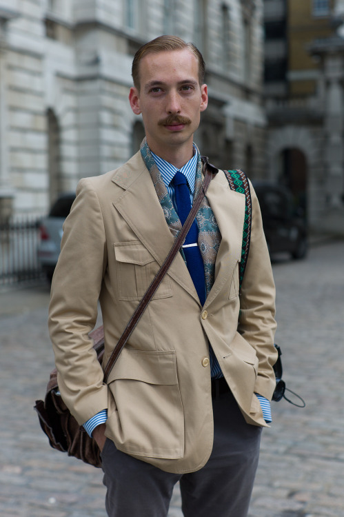 Vintage safari street style at #LFW combines menswear classics with perfectly hand-picked accessories. The lightweight 4-pocket jacket is a great example of functional, military-inspired tailoring, while the print scarf and woven camera strap offset that dapper Bengal stripe shirt and tie with a well-travelled edge. WGSN street shot, London Fashion Week