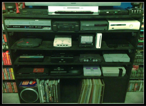 Here is my hooked-up-and-ready-to-play console collection. Top Row: DVD/VCR, Panasonic 3DO FZ-1, Philips CDi 490, X-Box 360. Second Row: Atari Jaguar, Sega Dreamcast, Nintendo Gamecube, Nintendo Wii, Playstation 2 (slim). Third Row: Atari 2600 Jr, Sega Saturn (MK-80001), Nintendo 64, Playstation 1. Bottom Row: Sega Master System, Sega Genesis (Model 2) with 32x & Sega CD (Model 2), Super Nintendo, NES. All the consoles are hooked up at ready to go via 3 switchers, 2 surge protectors, and their own power circuit which has a switch behind the TV.  Cabinet was again custom made by my dad and me.